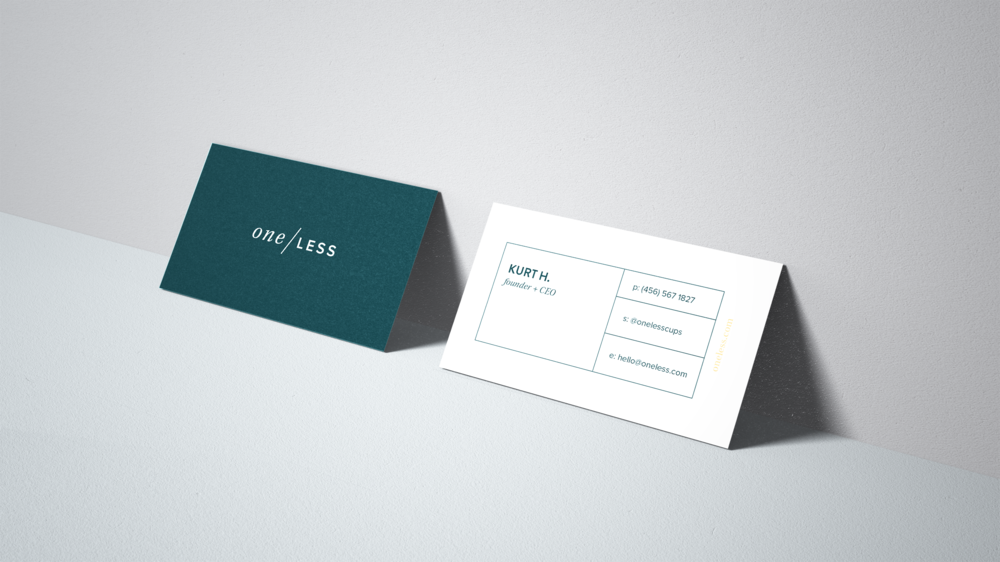 ocean blue business card for One Less leaning against a wall background