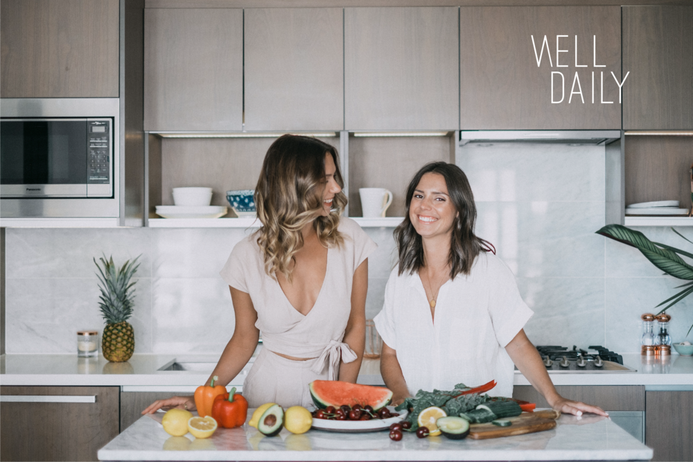 Well Daily word mark logo on a photo by Marcy Media of Brianna and Kylie in a kitchen with lots of fresh produce.