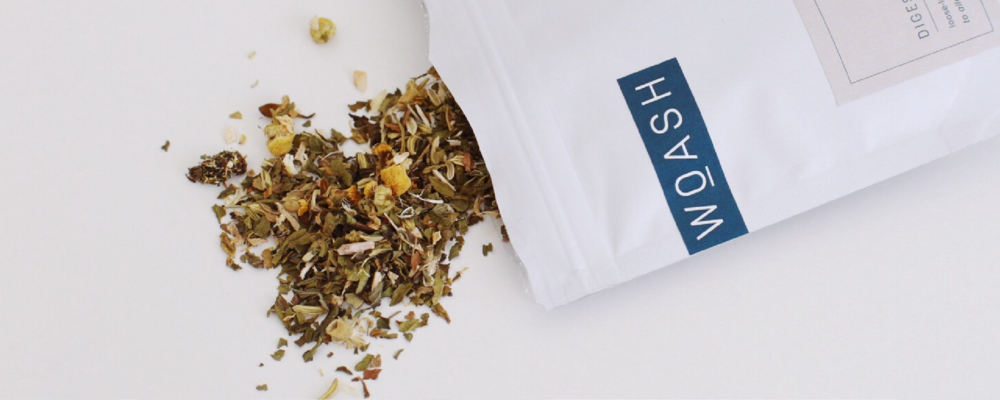 Woash Wellness white herbal tea packaging shown next to a mug