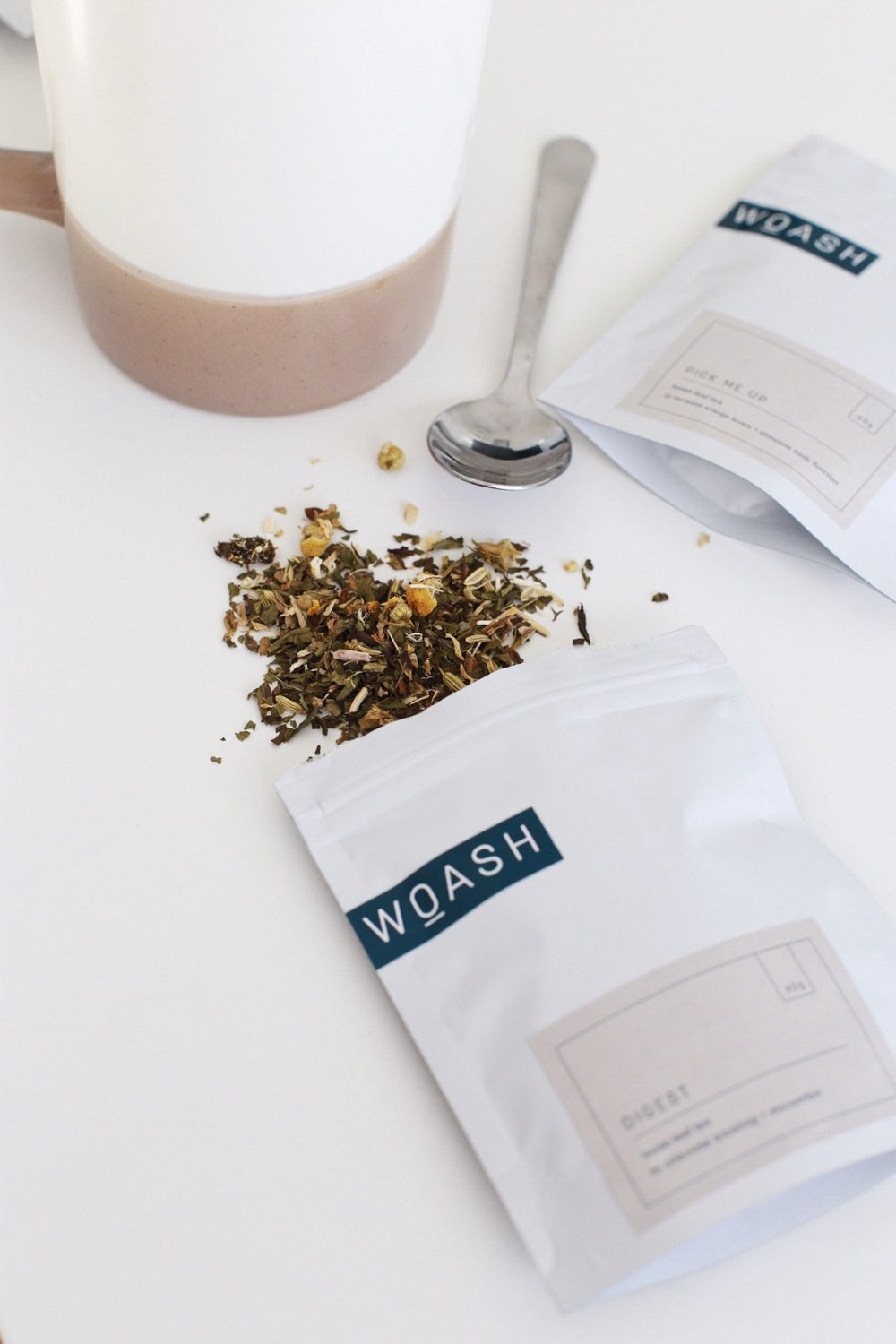 Photo of the white packaging with blue logo designed for Woash Wellness with tea spilling out of the bag next to a metal spoon.
