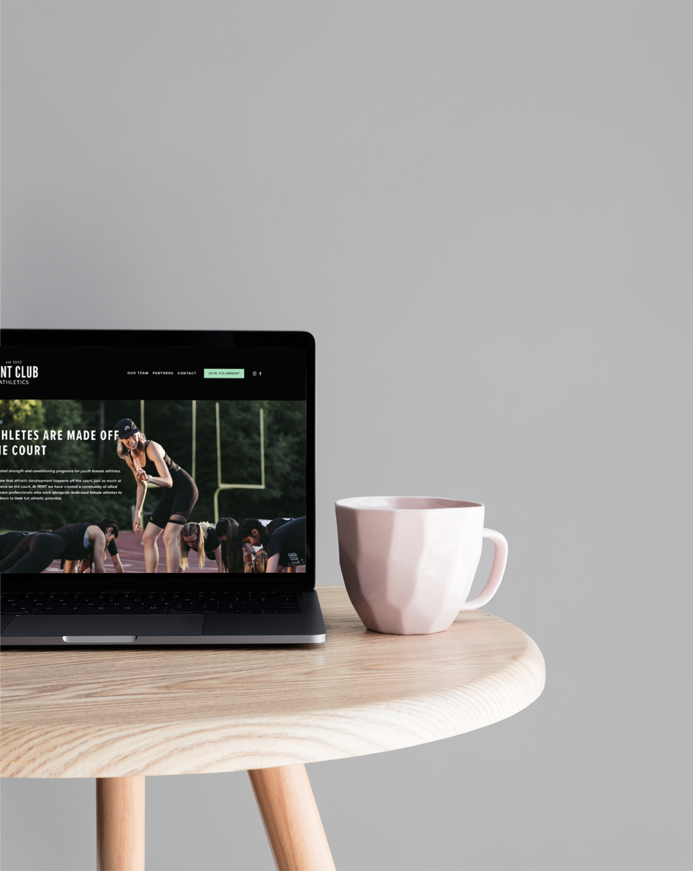 Mint Club Athletics website on a laptop sat on a wooden table with a pink coffee mug.
