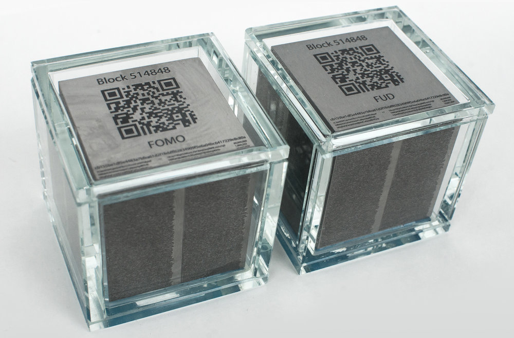 The Cubes - Two 5x5x5 cm tungsten*cubes engraved with Bitcoin block 514 848 transaction hashes encapsuled in glass. Both topsides are engraved with the same public Bitcoin address. The corresponding private key, which is necessary to withdraw the monetary value,is sealed inside a 200 NOK bill glued to the cube and to the glass that they are encapsuled in. The serial number of the 200 NOK bill inside FOMO is 2401224579 and the serial number inside FUD is 2401224580. The two pieces are identical except for their engraved names: FUD and FOMO**.* Tungsten has almost the same density as gold and is used by the mining industry due too its hardness. Bitcoin is created by a process called mining and is by many considered to be a store value such as gold. Each sculpture weighs 2.7 kg.** Fear, Uncertainty and Doubt (FUD) and Fear Of Missing Out (FOMO) are terms often used in connection with investment to describe selling and buying behaviour that drives prices up or down.