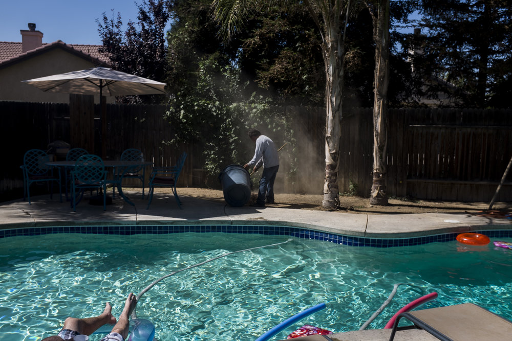 Eduardo tends to a client's backyard by cleaning up trash while the client, a police officer, relaxes in his pool in Bakersfield, CA. Photographed on June 19, 2014.
