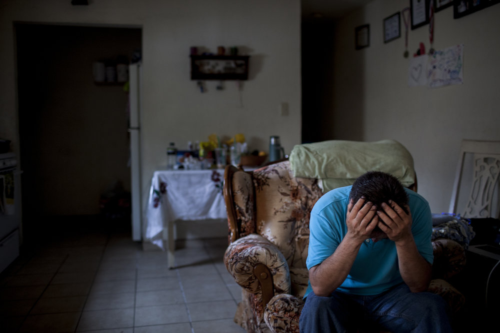 Eduardo sulks his head inside his Bakersfield home after recounting the ordeal he had to go through when he first crossed into the United States by himself without his family in 2000 from Mexico. Photographed on September 2, 2013.