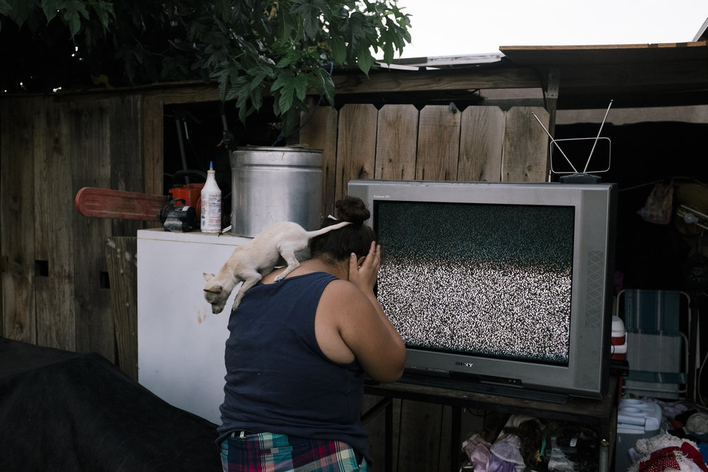 Blanca stands in her backyard in her Bakersfield home during summer break in front of a television that a client of her father's gifted to the family. Photographed on June 20, 2014.