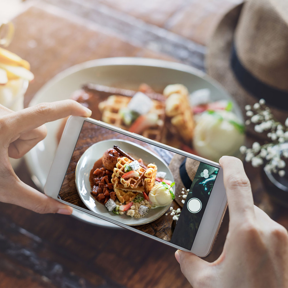 Young woman taking photo of food with smart phone in restaurant-1.jpg