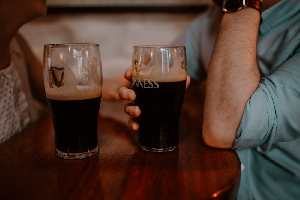irish couple have a pint of guiness before their beach engagement session in Ballycastle