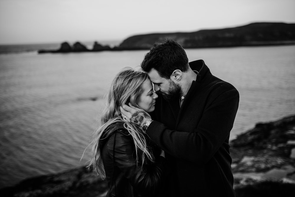 beautiful moment at the coast between a couple in black and white