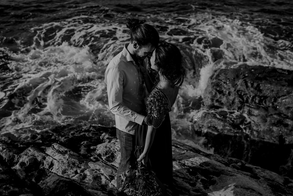crashing waves around a couple during their engagement session on the North Coast