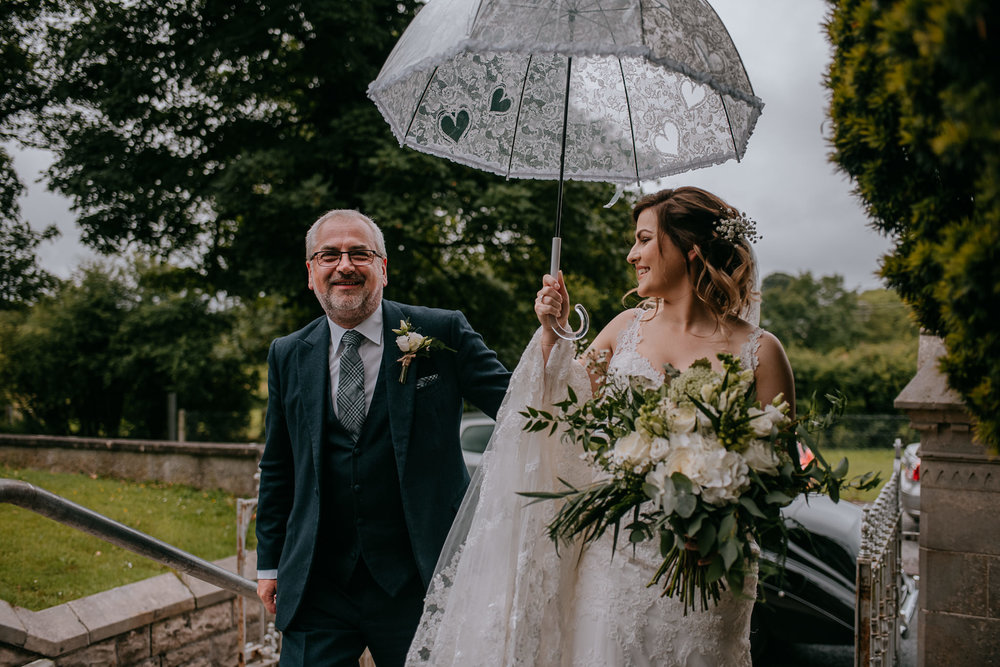 bride and father arrive at ceremony umbrella Northern Ireland Wedding Photographers