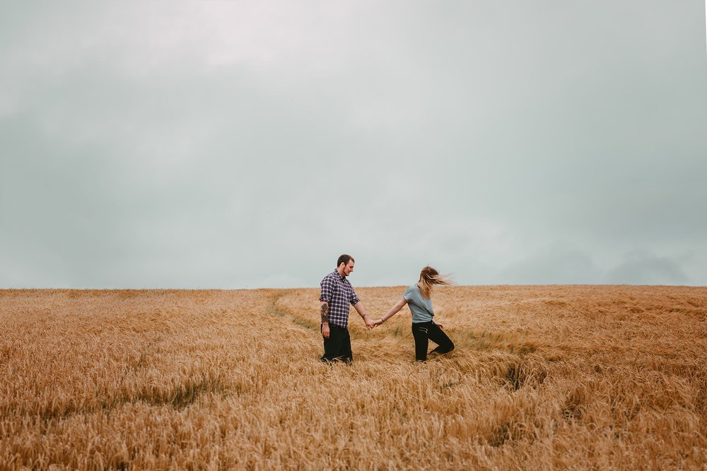 walking in field cute hipster couple engagement photos northern ireland