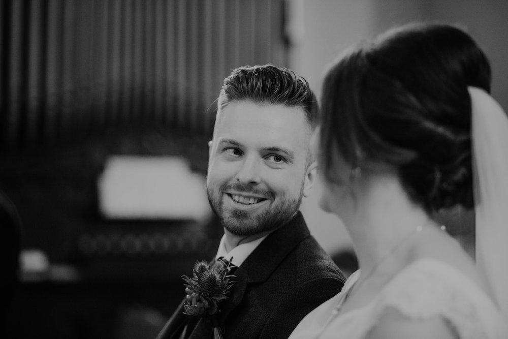 groom looks at bride ceremony