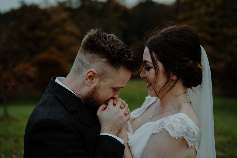 groom kissing brides hands  wedding at lissanoure castle