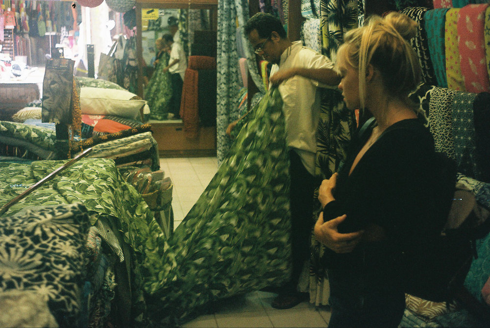 Taylor watches one of our local Balinese suppliers, Wayan, cut fabric to be used as lining for the 'Castaway' Rattan Bags.