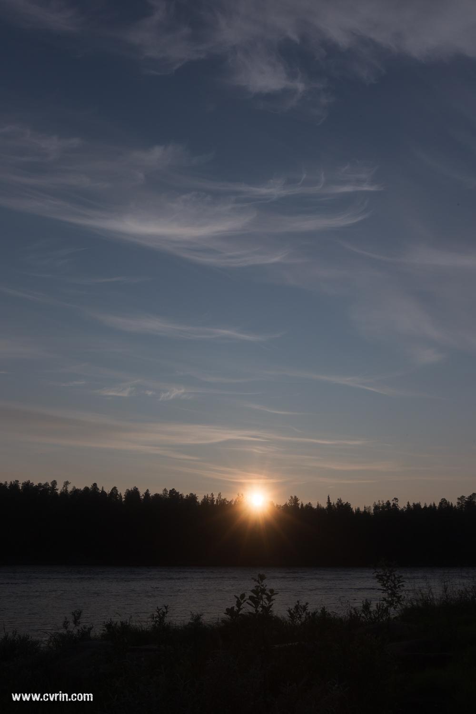 Le soleil de minuit vu depuis la Finlande par-dessus le fleuve Torne, frontière naturelle avec la Suède