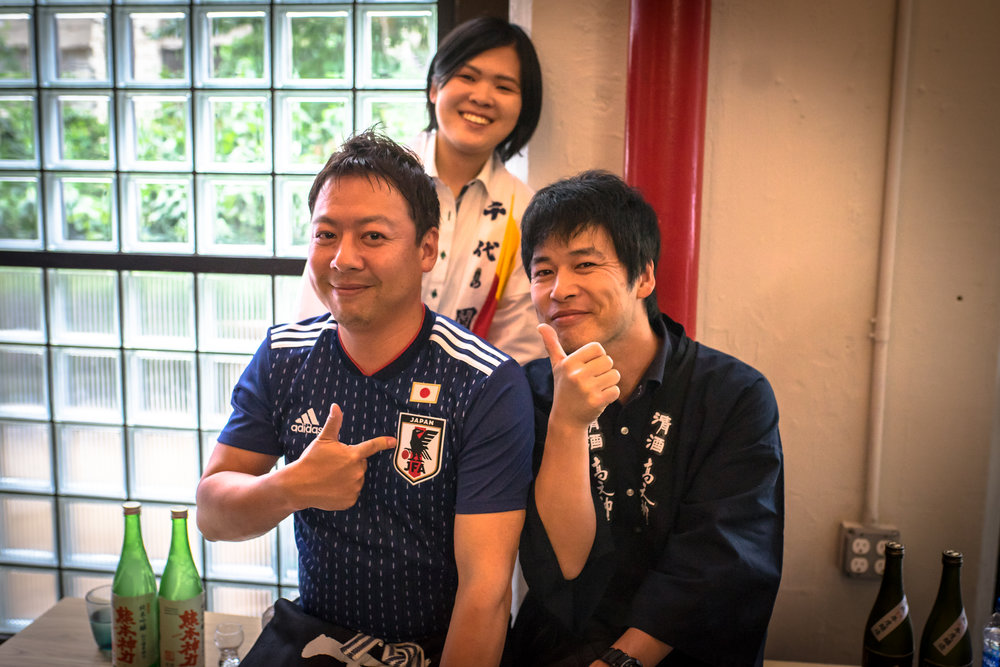 Sake brewers, Kensuke Shichida, Yaichi Doi, and Yuri Honda take a moment to relax after pouring sake for thirsty customers
