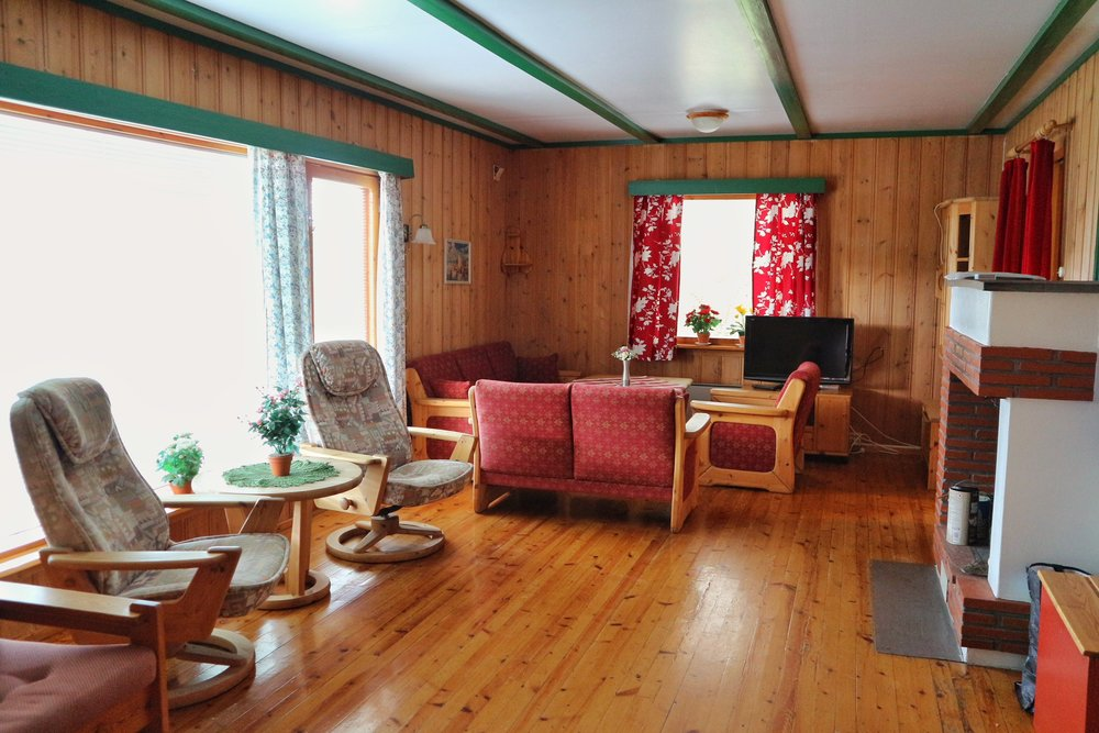 Stue med peis og store vindusflater. Bilde tatt fra inngang til soveromsfløy. Inngang til kjøkken til høyre bak peisen.