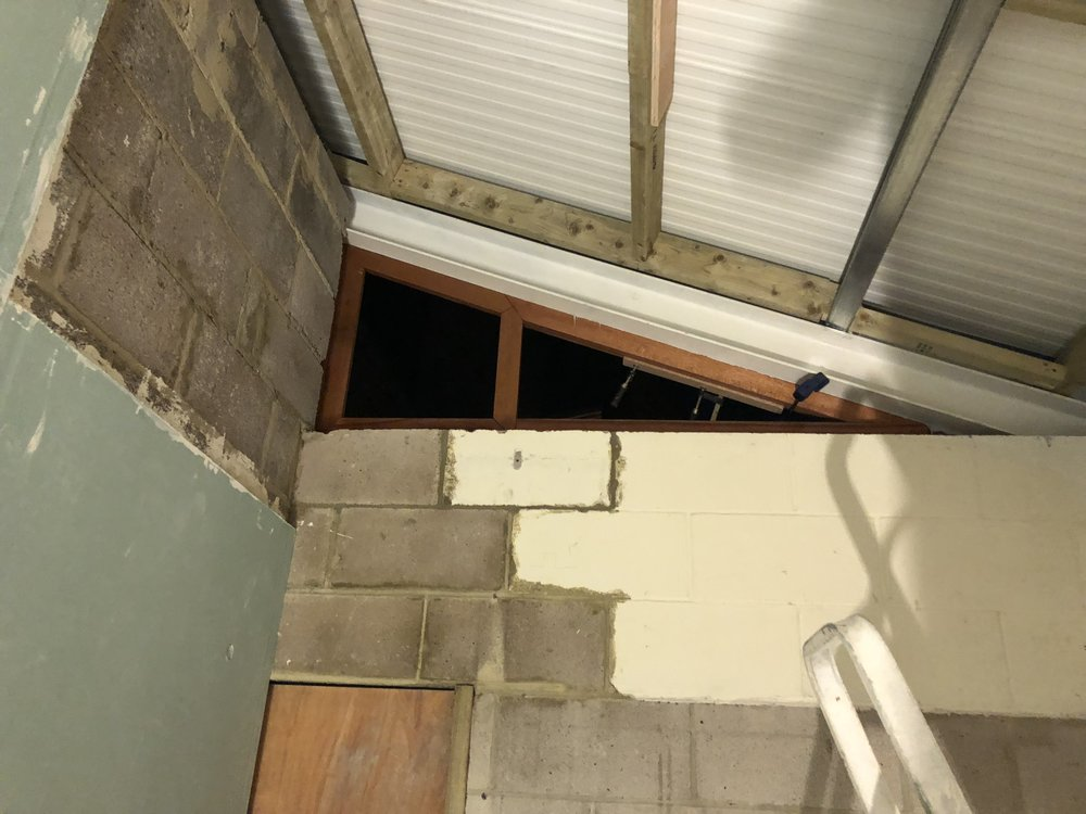 Fitting the high window frame to the new physio's room, viewed from inside.
