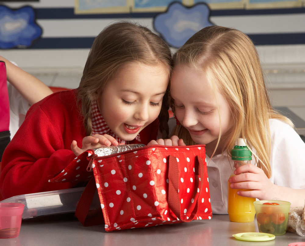 two girls looking in their lunch box at school