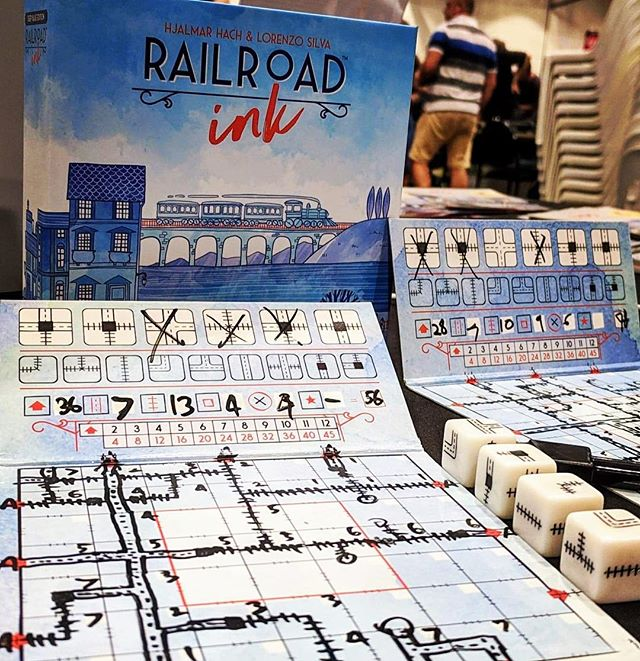 First play of #RailroadInk at #cancon2018 and it's AMAZING! 🚂 ⭐️⭐️⭐️ Each round, you roll the dice and draw those rails and highways on your board. You score big for making a sprawling, complex network but if you get too ambitious then you'll lose points at the end of the game for any loose ends you haven't connected. 🚂🚂🚂 This game is simple to teach, but every turn is packed with interesting choices and strategy. Each of the mini expansions can also be added in (rivers or lakes in #RailroadInkBlue) to add another element to balance in your network. ⭐️⭐️⭐️ We haven't had a chance to try #RailroadInkRed yet, but it includes meteors and lava as the two mini expansions. Fans of more aggressive gameplay, or players who like mitigating damage (eg #Pandemic) might want to get the #BlazingRed edition instead. (Or get both like we did so you can play with up to 12 players!) 🚂🚂🚂 If you're a fan of #rollandwrite games, or you just like creating networks, you definitely need to play this! ❤️ . . . . #railroadinkdeepblue #railroadinkblazingred #railrodinkred #cancon #rollandwritegame #boardgamesofinstagram #boardgamephotography #boardgamephotos #tabletopphotography #boardgames #boardgame #boardgaming #boardgamenight #gamenight #boardgamegeek #analoggames #tabletop #tabletopgames #tabletopgaming #bgg #brettspiel  #cmon #horriblegames