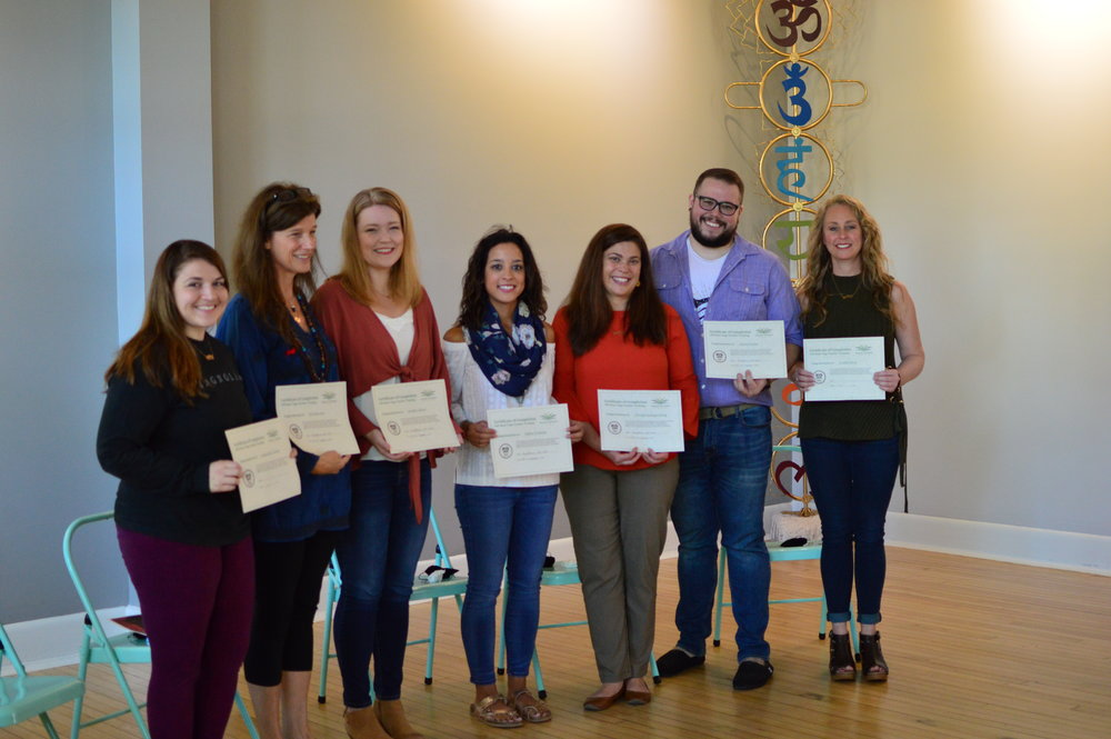 Photo of training session participants with their certification awards.