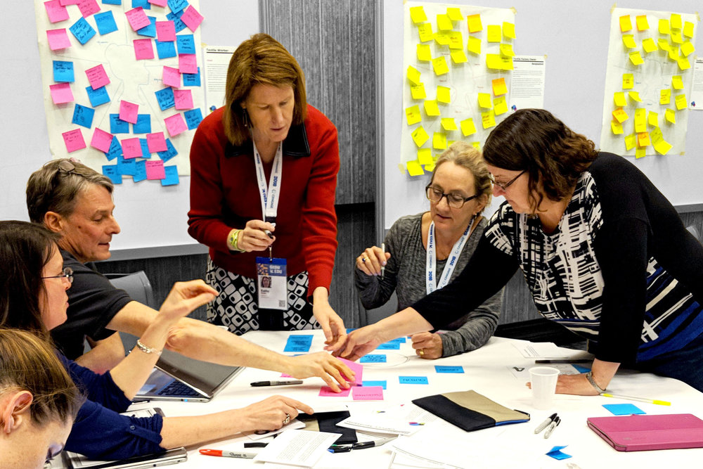 A group of participants negotiates stakeholder placement via post-its and paper at SXSWedu.