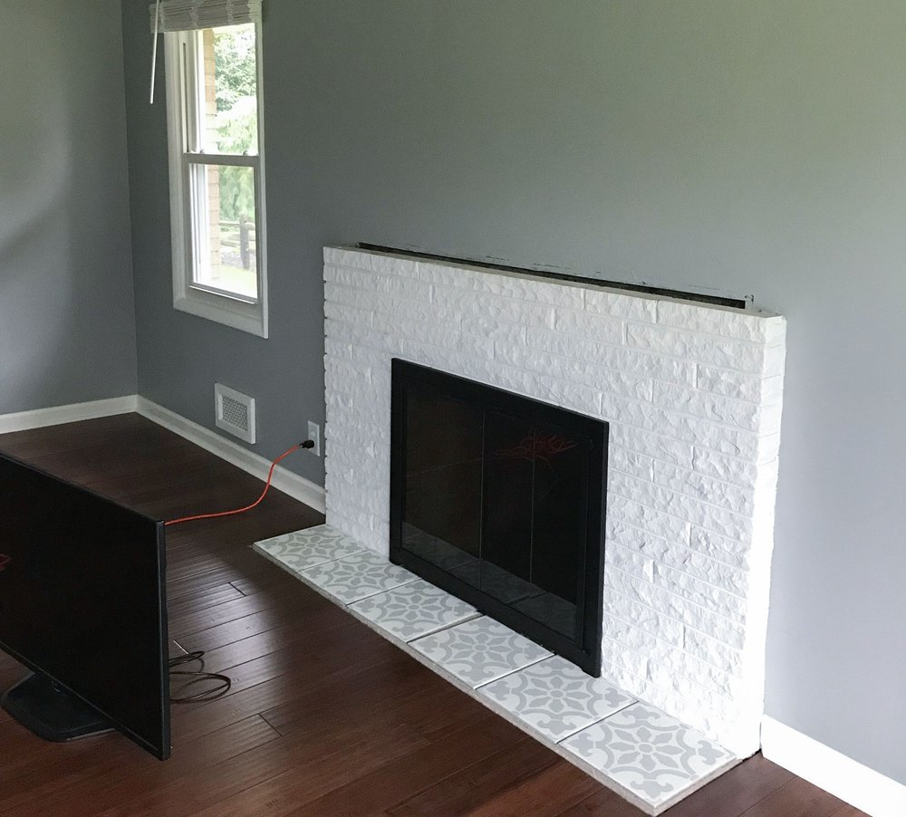 Before photo of a white fireplace in a living room,