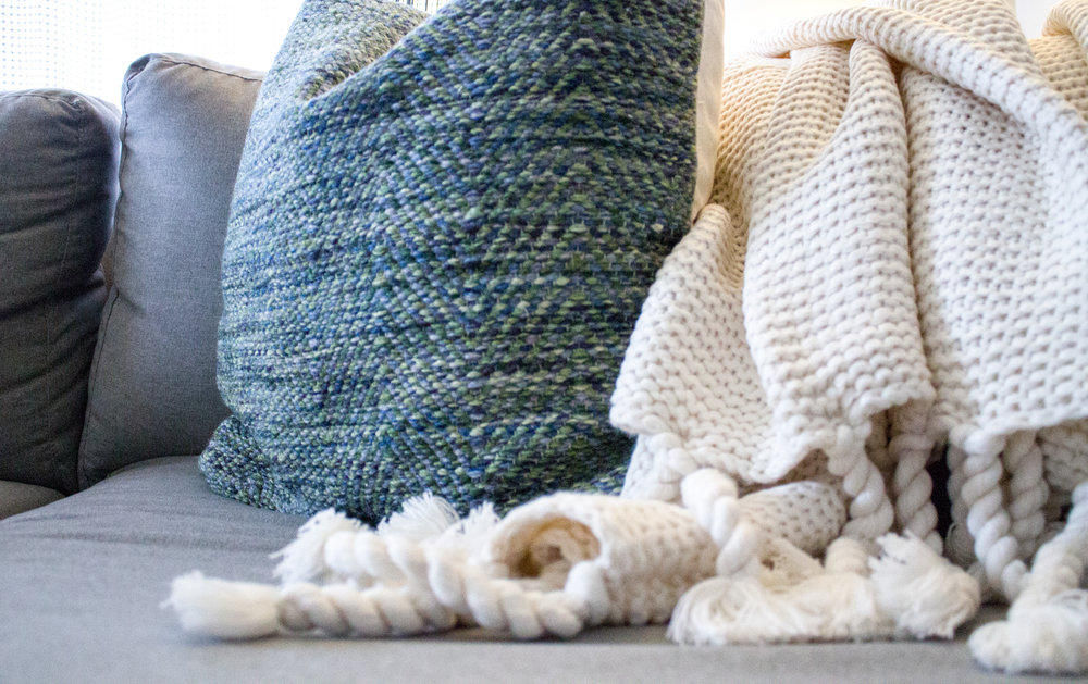 blue and green threaded throw pillow and chunky white throw blanket, abbreviated design provides online interior design services in Grand Rapids Michigan,