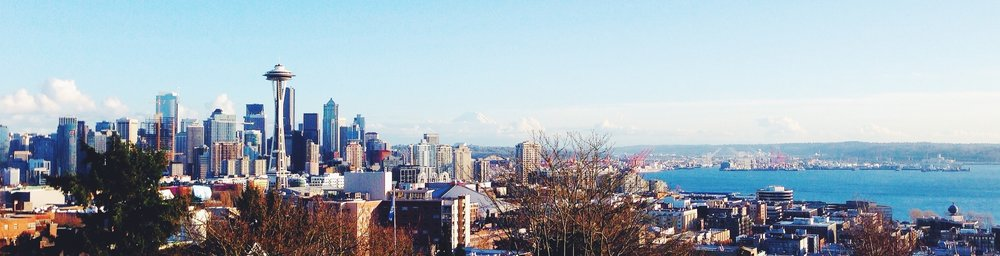 Image description: Distant view of downtown Seattle on a bright, sunny day Photo by  Thorsten Beeck