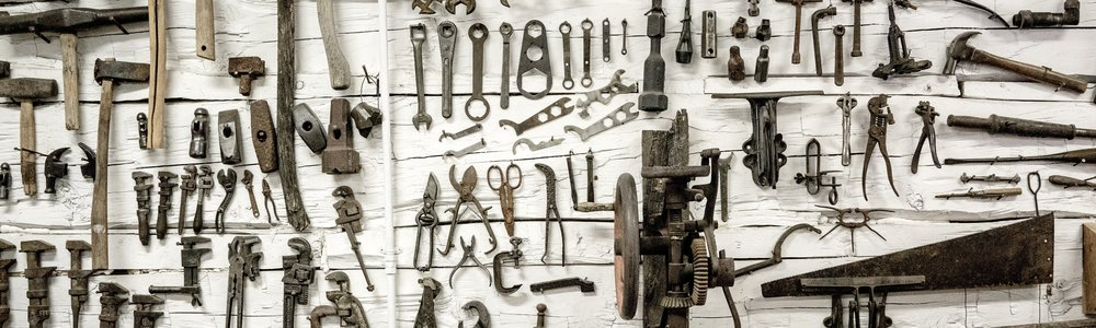 Image description: Wall covered in many hanging miscellaneous tools Photo by  Lachlan Donald