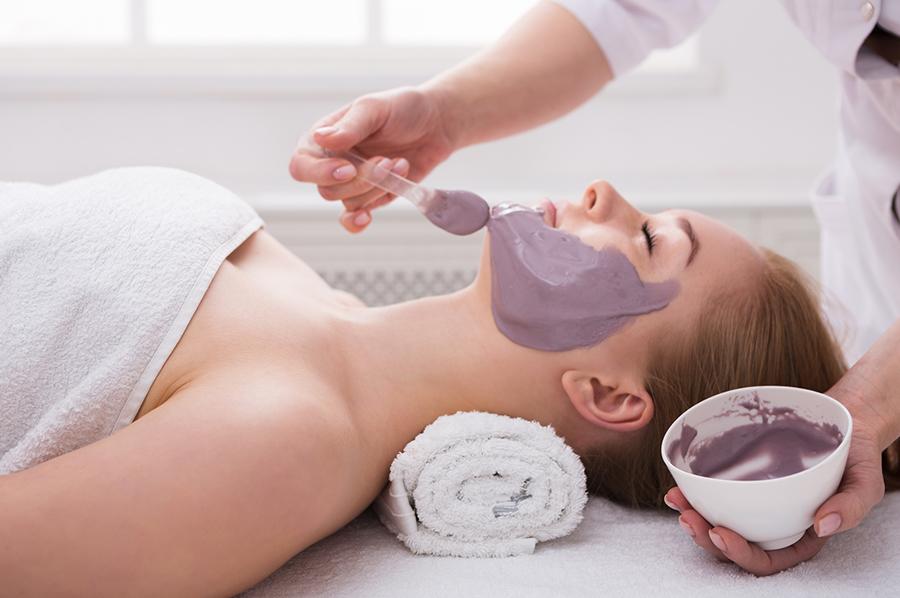 girl at a spa receiving a facial treatment