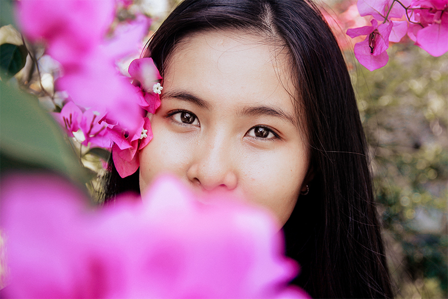 Beautiful girl with long black hair posed by flowers