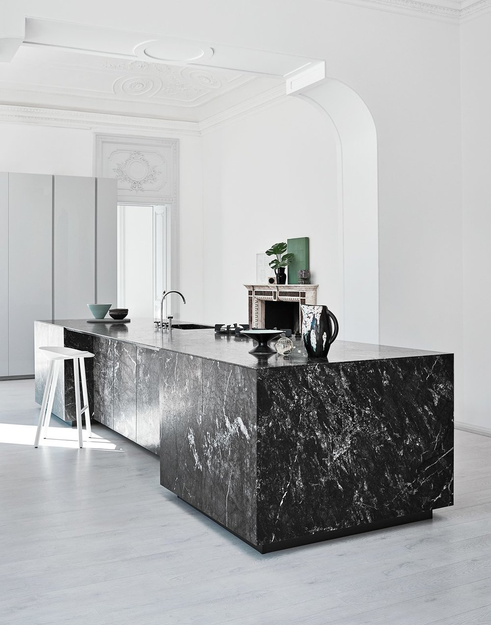 The choice of material and design for this kitchen island has a powerful and sculptural appearance, set in a period property, creating a contrasting unexpected element. The island is in Grey Saint Laurent Dark Marble.