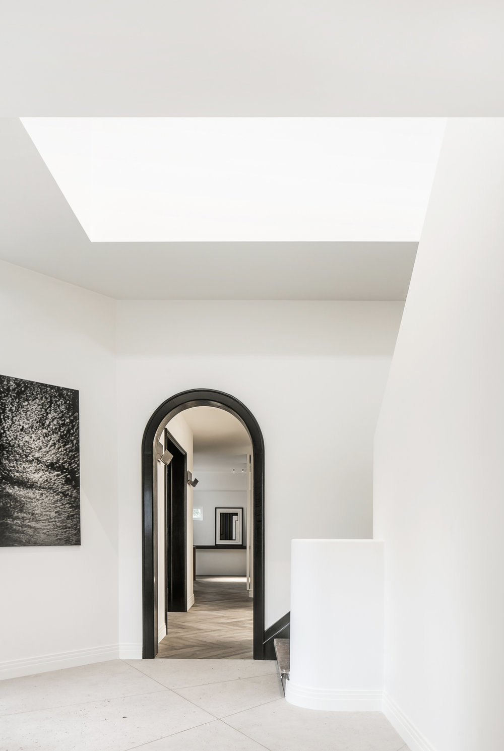 Tall ceiling and sharp lines softened by the black arched curve that creates a framed feature.