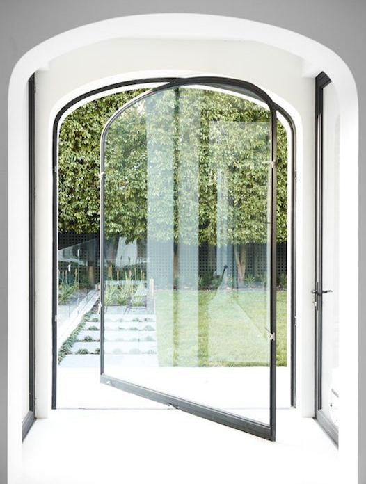 Arched Pivot Door - Old shape meets new technology. The arched black framed pivot door makes for a great statement leading into your garden