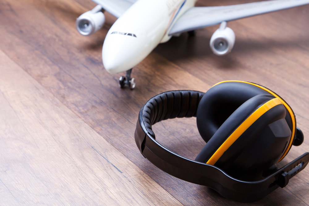 Ear protection on the wooden floor with airplane in back