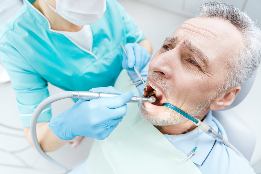 Cropped shot of professional dentist curing scared mature patient in dental clinic