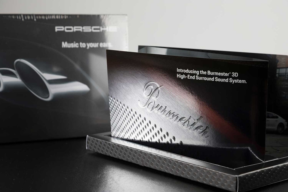 Porsche Cars of North America (PNCA). - PNCA was looking to promote the new, Burmester® High-End 3D Surround Sound System for its Panamera luxury sedan, and C-K invited Adams to bid on a classy direct mail piece that would help bring the sound system the exposure it deserved.