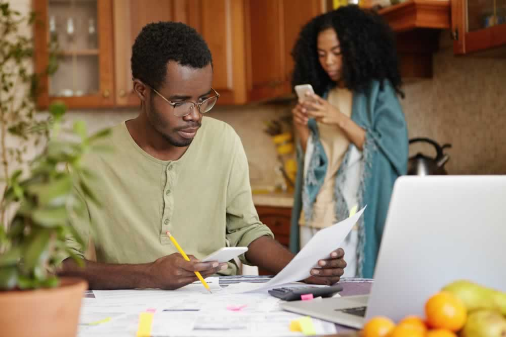 serious-and-concentrated-young-african-american-male-wearing-spectacles-paying-bills-online-using