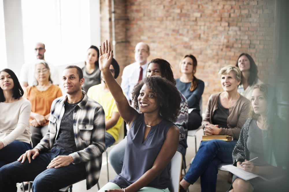 stock-photo-audience-meeting-seminar-arms-raised-asking-concept