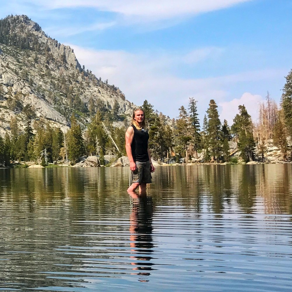 standing on a rock in the middle of the lake