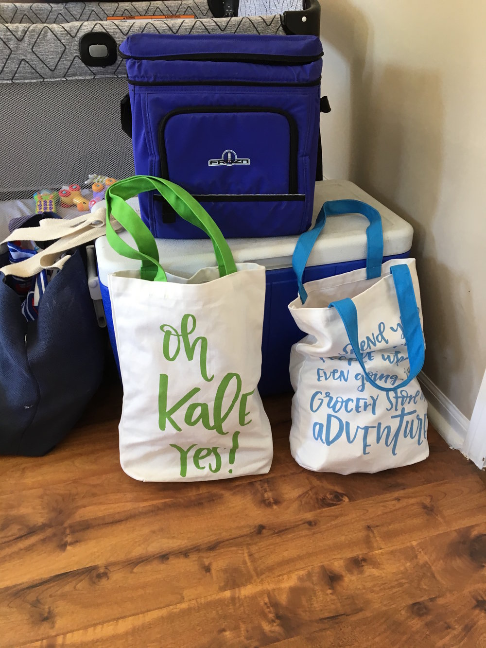 Two tote bags, a cooler, and a pack and play