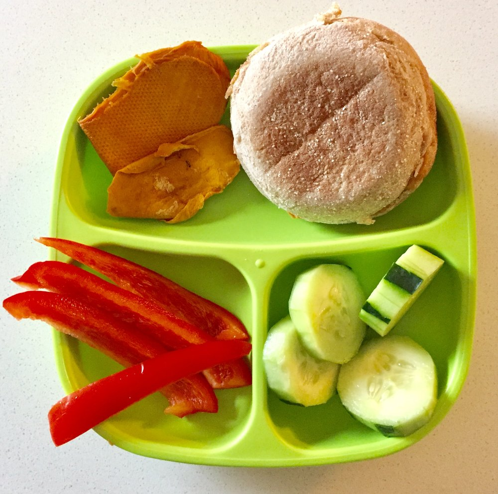 Peanut butter and honey sandwich in a whole wheat english muffin, cucumbers, red bell peppers, and dry mango for dessert.