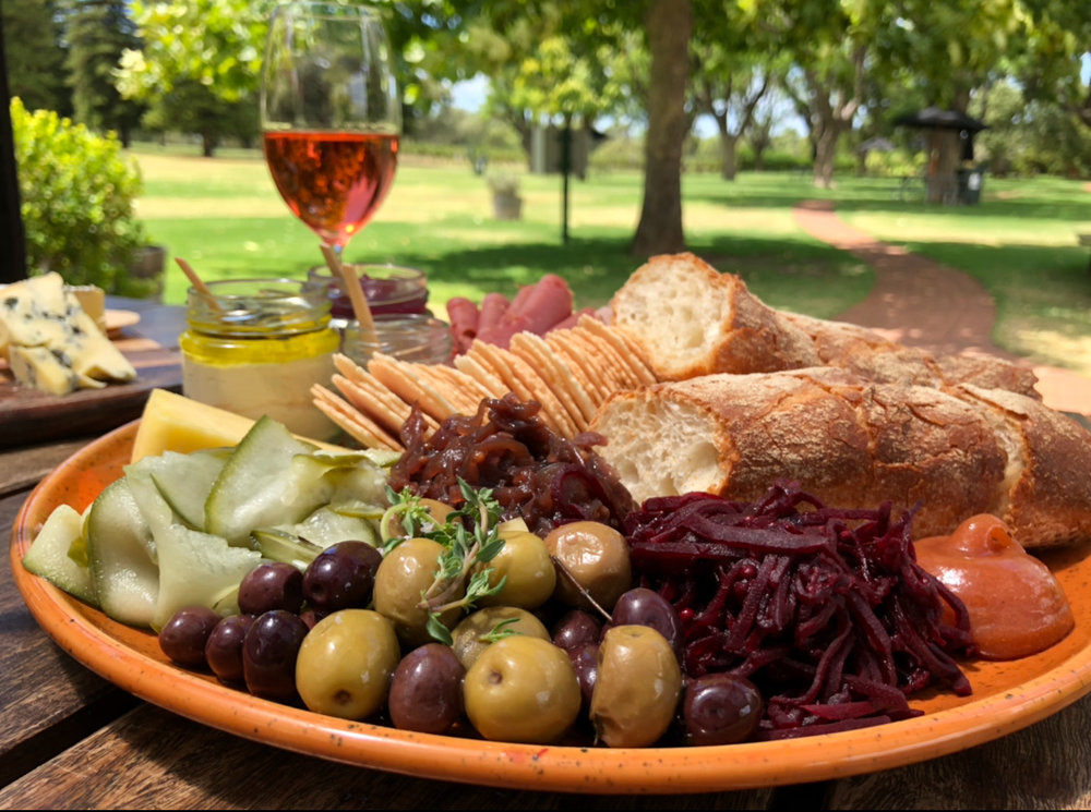 (To share) The Ploughman's Platter: pork terrine, leg ham, corned beef, onion jam, beetroot relish, house pickles, aged cheddar cheese, olives, almond hommus, dukkah, baguette, crackers paired with a bottle of Small Batch Pinot Grigio$58 - Availability: Lunch