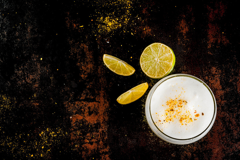 Foamy drink on wooden background with lemon slices