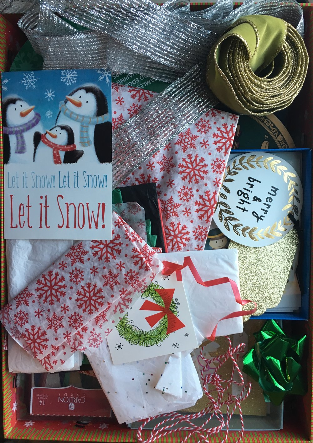 A reusable gift box filled with Christmas cards, string, old tags, and bows