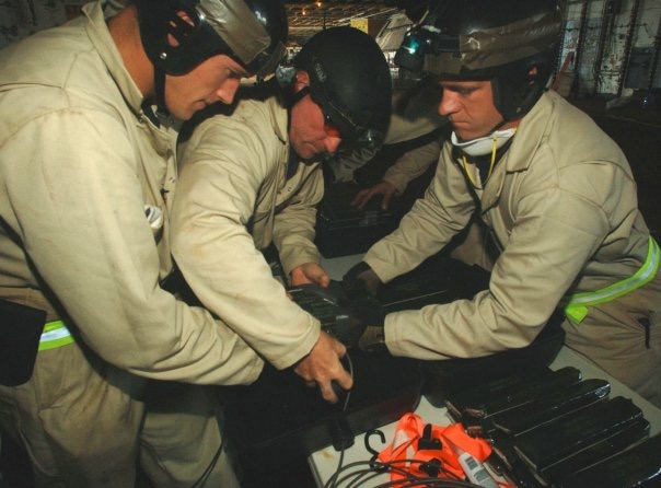 Me on the right along with fellow EOD team members building water proof charges to skuttle the USS Oriskany.