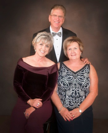 Tom Travis (standing), Donna Travis (seated left), and Barb Travis (seated right)