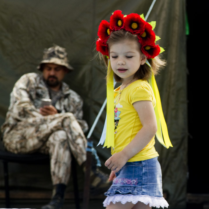 A young girl wearing a Vinok, a wreath of poppies that is part of traditional Ukrainian folk costume, explores the wreckage of the barricades and tent city on the Maidan in central Kyiv, while a dissenter in camouflage relaxes outside his tent.