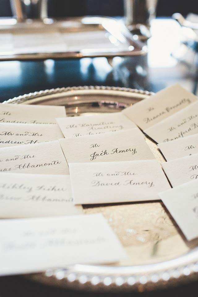 Escort cards displayed beautifully on an antique tray for guests
